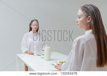 Two mysterious women sitting at the table with food and drink over grey background