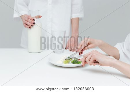 Close-up of hands holding knife and fork over vegetable salad and glass of milk during lunch over gray background