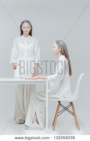 Two beatiful unusual women having a meal at the table over gray background
