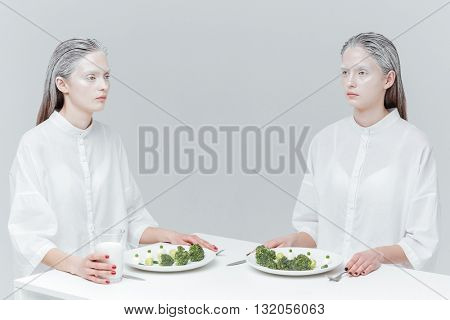 Two pretty fashion women eating healthy food at the table  over gray background
