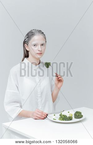 Trendy beautiful woman having lunch at the table over gray background