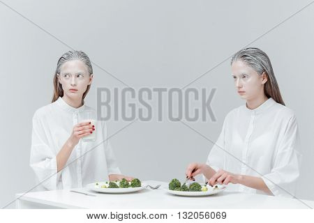 Two beautiful young women eating at the table over gray background