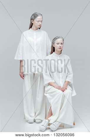 Two fashion mysterious women in white dress over gray background