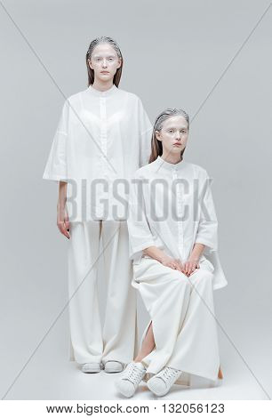 Two beautiful mystical alien women in white dress over gray background