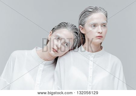 Close-up portrait of two beautiful fashion women in white shirts over gray background