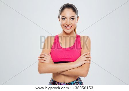 Smiling sports woman standing with arms folded and looking at camera isolated on a white background