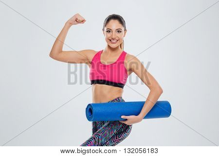 Happy fitness woman holding yoga mat and showing her biceps isolated on a white background