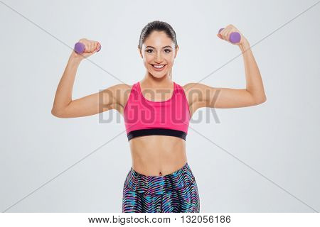 Smiling fitness woman workout with small dumbbells isolated on a white background