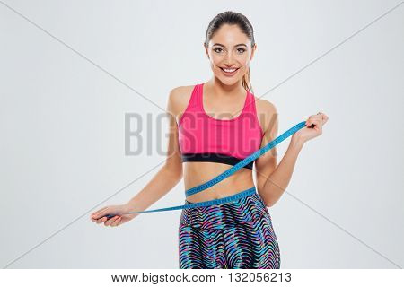 Smiling fitness woman measuring waist with tape isolated on a white background