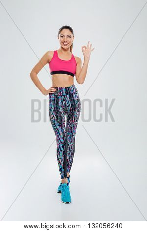 Full length portrait of a sports woman showing ok sign isolated on a white background