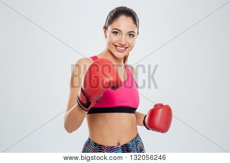Happy woman in boxing gloves looking at camera isolated on a white background