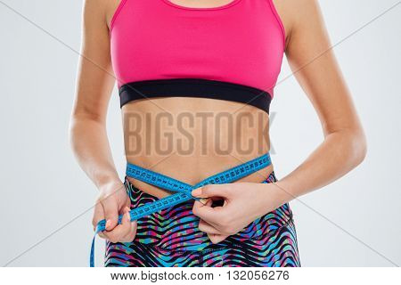 Cropped image of a sports woman measuring waist with tape isolated on a white background