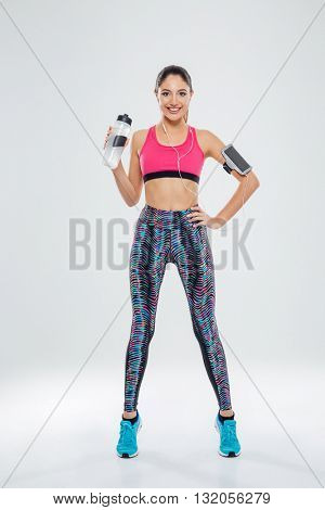 Full length portrait of a happy sports woman holding shaker with water isolated on a white background