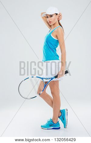 Full length portrait of a pensive woman with tennis racquet standing isolated on a white background