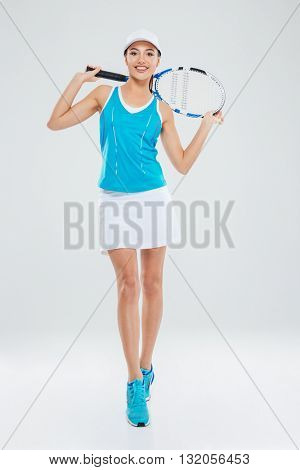 Full length portrait of a smiling woman with tennis racquet looking at camera isolated on a white background
