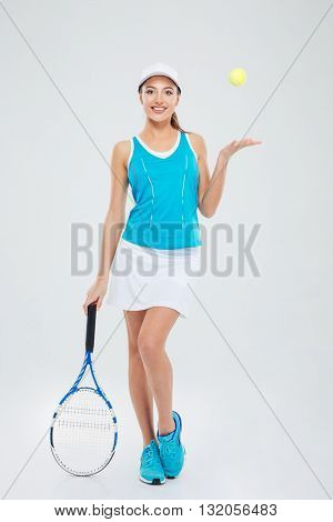 Full length portrait of a happy woman holding tennis racquet and ball isolated on a white background