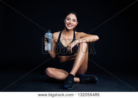 Happy fitness woman sitting on the floor with bottle of water on black background