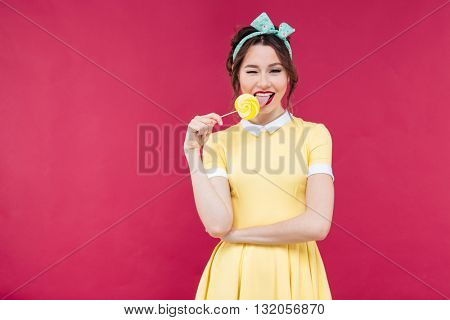 Happy charming pinup girl eating sweet lollipop and winking over pink background