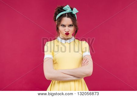 Sad frowning pinup girl in yellow dress standing with arms crossed over pink background