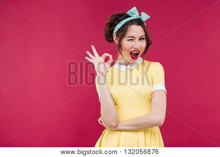 Happy attractive pinup girl in yellow dress showing ok sign over pink background