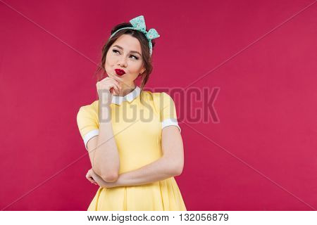 Happy thoughtful young woman standing and thinking over pink background