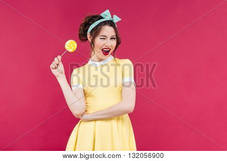 Cheerful charming pinup girl with yellow lollipop standing and winking over pink background