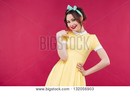 Smiling beautiful young woman in yellow dress standing over pink background