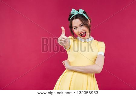Cheerful lovely young woman in yellow dress showing thumbs up over pink background