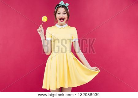 Cheerful cute pinup girl standing and holding yellow lollipop over pink background