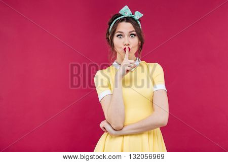 Beautiful cute pinup girl in yellow dress showing silence sign over pink background
