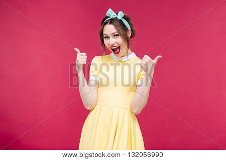 Cheerful excited pinup girl showing thumbs up over pink background
