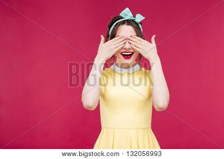 Happy attractive pinup girl covered her eyes by hands over pink background