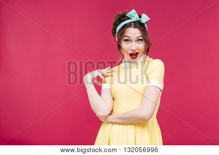 Amazed happy pinup girl in yellow dress standing and posing over pink background