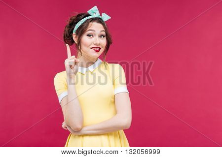 Attractive smiling pinup girl in yellow dress pointing up over pink background