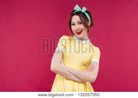 Cheerful lovely pinup girl in yellow dress standing and smiling over pink background