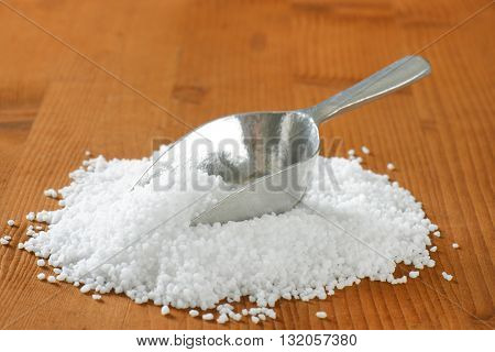 heap coarse grained salt and metal scoop on wooden table