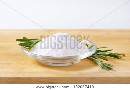 bowl of coarse grained salt and rosemary on wooden cutting board