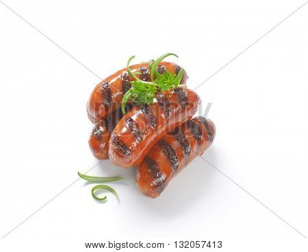 grilled short sausages with herbs on white background