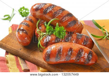 grilled short sausages on wooden cutting board - close up
