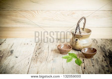 Tea cups with teapot on old wooden table.