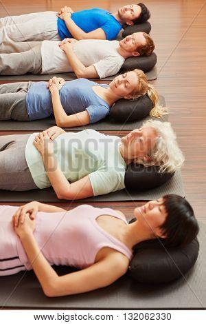 Senior meditating in yoga class at fitness center