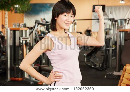 Successful woman showing her muscles at the gym