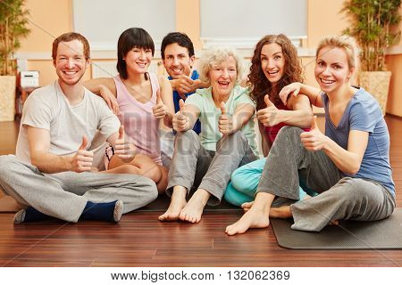 Happy group of friends with thumbs up in pilates class