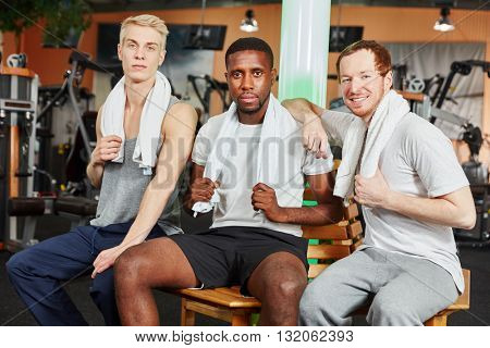 Group of men are friends ahd rest after training at the gym