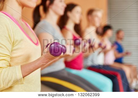 Lifting weights in a pilates class at fitness studio