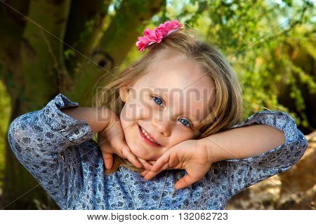 A sweet little girl with blond hair and blue eys poses with her hands under her chin. Her head is tilted to the side and she has a sideways grin.