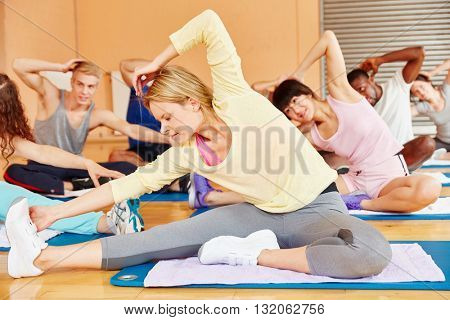 Group making gymnastics exercise in fitness center