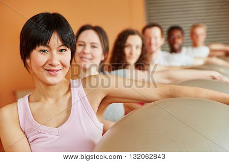 Woman with gym ball in pilates class at fitness studio