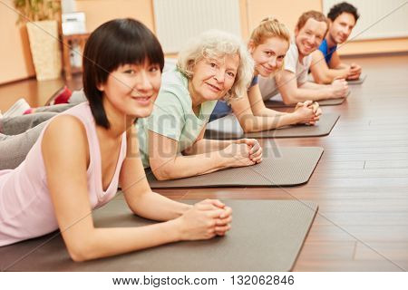 Group in yoga class with senior citizen at health club