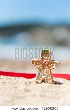 Christmas ginger bread man standing at summer beach